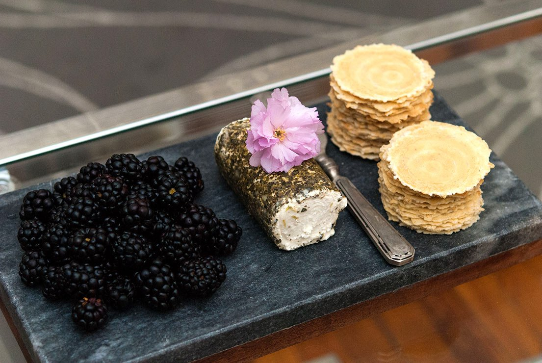 A cheese plate with blackberries, goat cheese and crackers on a dark slate