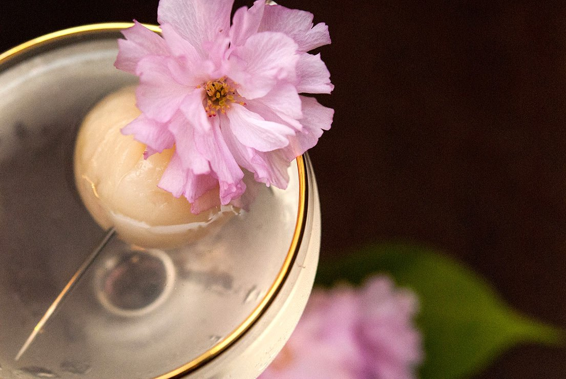 A closeup of a lychee cocktail garnished with a lychee and cherry blossom.