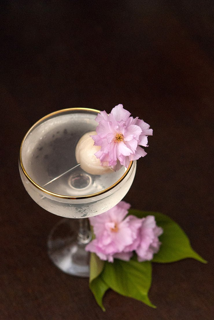 A lychee cocktail on a dark table, garnished with a lychee and cherry blossoms.
