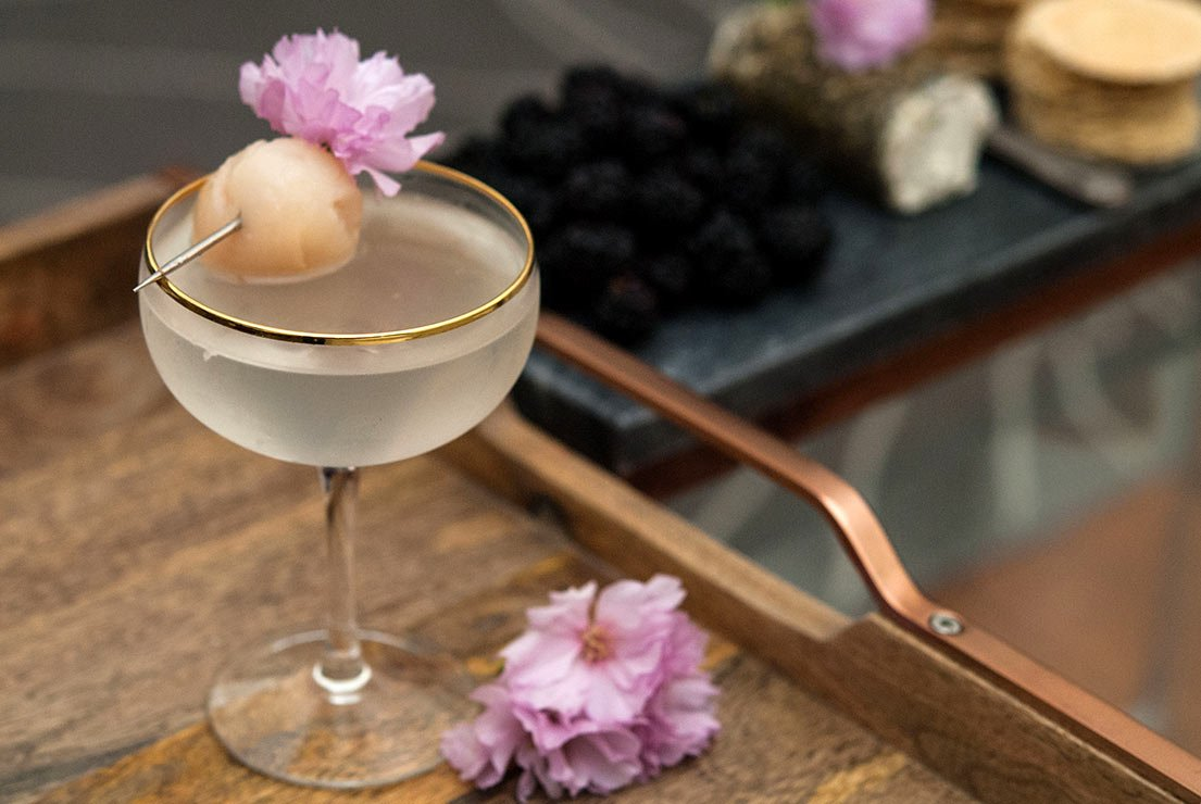 A lychee cocktail garnished with cherry blossoms and a lychee on a wooden tray in front of a cheese plate.