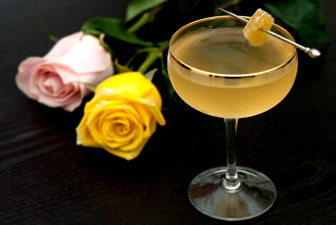 A cocktail in a coup glass, garnished with candied ginger on a black table next to 2 roses.