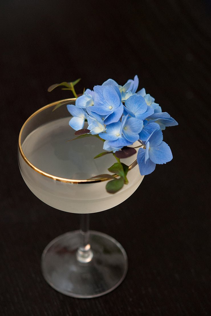 A cocktail with a gold rim, garnished with hydrangea flowers on a black table.