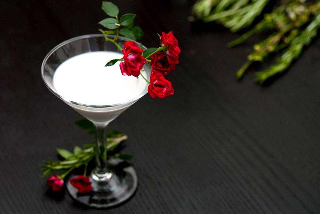 A white coconut cocktail in a martini glass, garnished with roses on a black table, and a few sprigs of rosemary in the background.