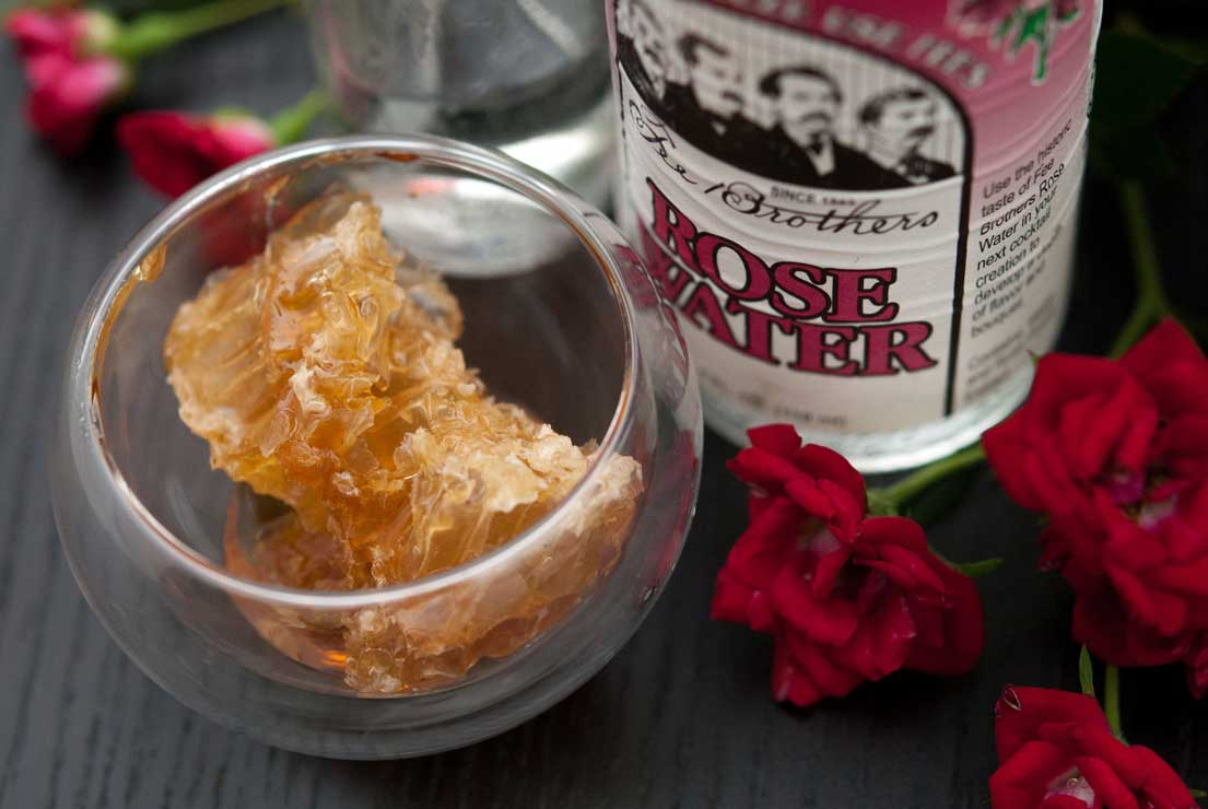 A small bowl of raw honey in a honeycomb next to a bottle of rose water on a black table with a few spray roses.