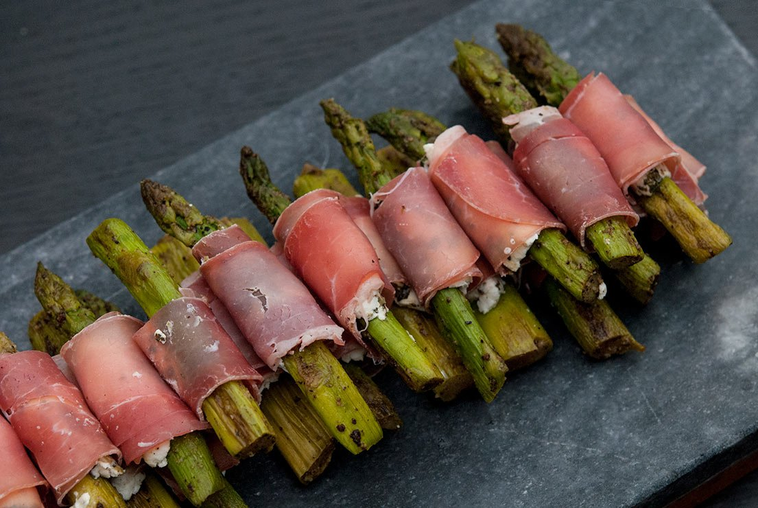 Small pieces of asparagus wrapped in prosciutto on a dark grey slate sitting on a black table