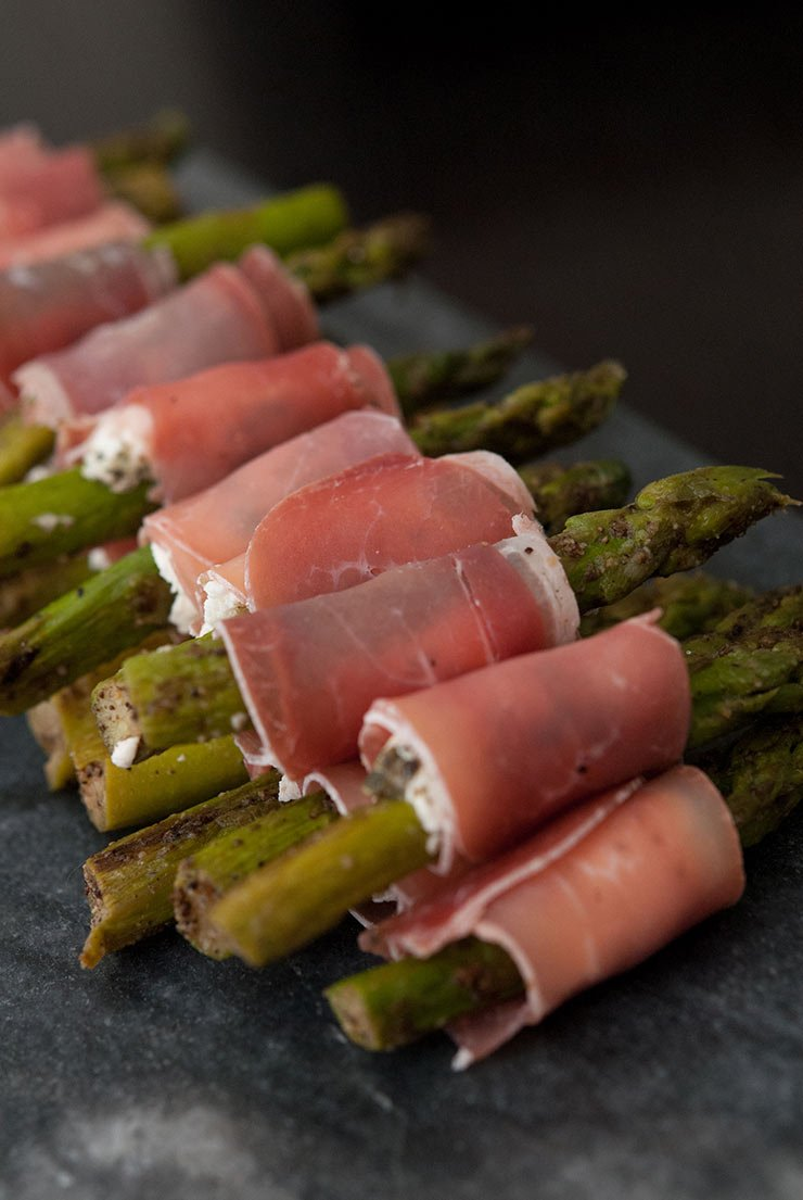 Prosciutto wrapped in asparagus on a dark slate.