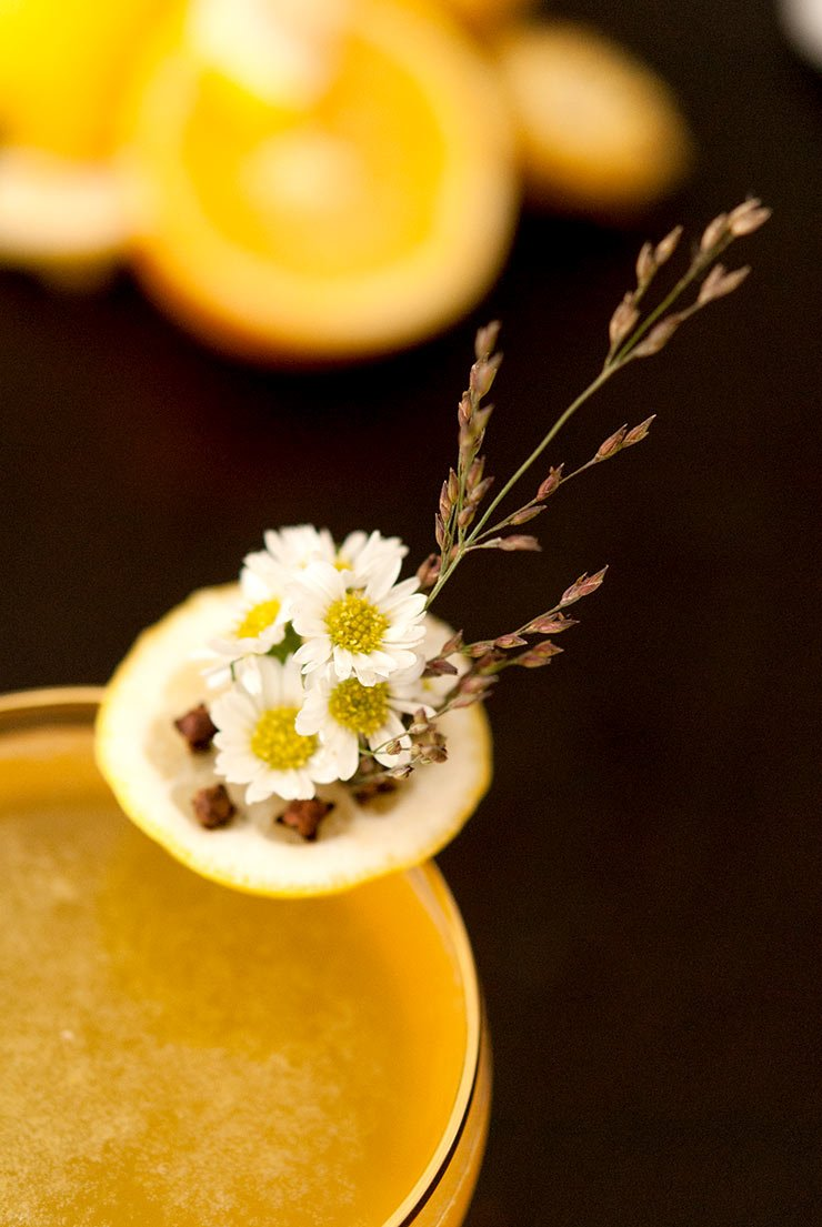 A closeup of a garnish with daisies, cloves and lemon on the edge of a cocktail glass on a black table with bright lemons in the background