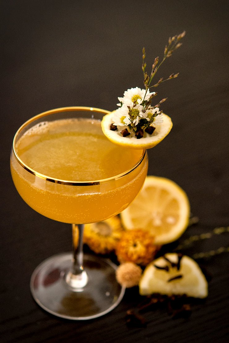 A cocktail in a glass with a gold rim, a garnish of daisies pressed into a slice of lemon with cloves, sitting on a black table with sliced lemons and dry flowers around it