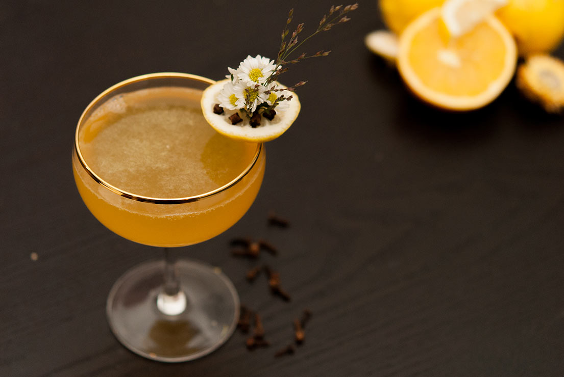 A cocktail in a glass with a gold rim, a garnish of daisies pressed into a slice of lemon with cloves, sitting on a black table with sliced lemons in the background