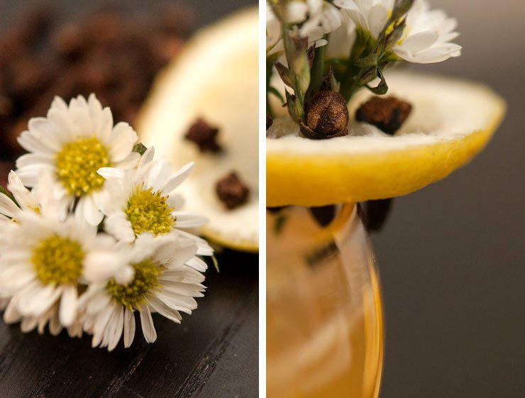A closeup of daisies on a black table side-by-side with an image of a slice of lemon on the edge of a glass with daisies and cloves pressed into it.